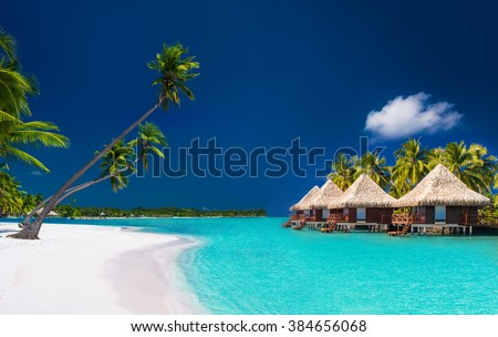 Beach villas on a tropical island with palm trees and white sandy beach - stock photo