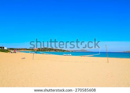 beach volley net and rubber boats in Porto Pollo, Sardinia - stock photo