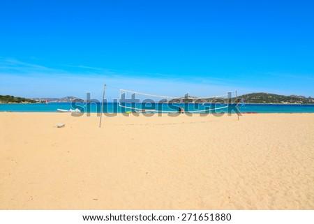 beach volley net and surfers in Porto Pollo beach, Sardinia - stock photo