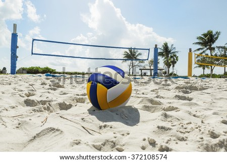 Beach volleyball ball in the foreground on the sand beach in the background volleyball net and palm trees, sunny day at the beach. Florida - stock photo