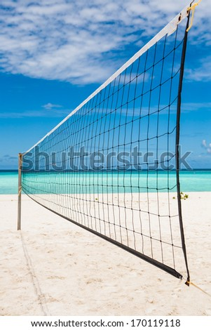 beach volleyball net with a turquoise sea and a blue sky with white clouds in summer - stock photo