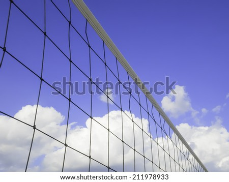 Beach volleyball net with blue sky, summer clouds, and copy space