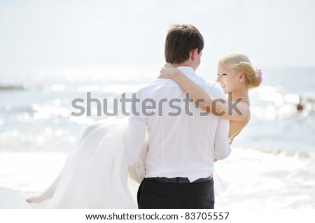 Beach wedding: bride and groom by the sea - stock photo