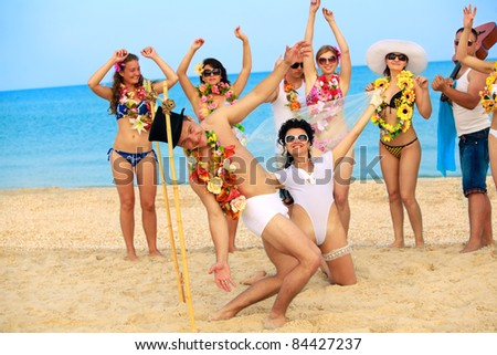 Beach wedding of happy newlywed couple have fun doing the limbo - stock photo