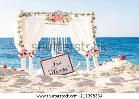 beach wedding set up, tropical outdoor wedding reception, beautiful cabana, wedding arch - stock photo
