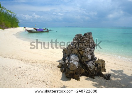 Beach with beautiful rock and moored boats