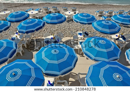 Beach with blue umbrellas near Promenade des Anglais in city of Nice, France. - stock photo