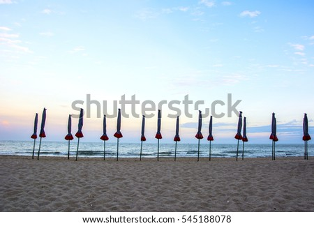 Beach with closed umbrellas