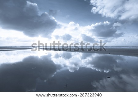Beach with clouds and the sun reflection on the water in a calm monochrome setting - stock photo