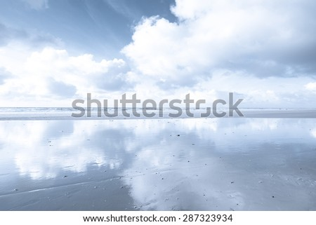 Beach with clouds and the sun reflection on the water in a calm, tranquil monochrome setting - stock photo