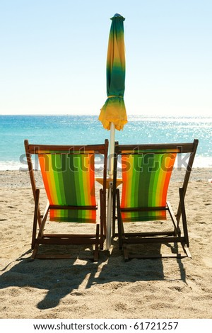 Beach with colorful chairs and umbrella - stock photo