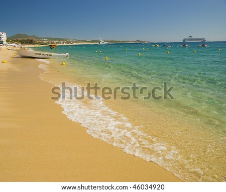 Beach with crystal clear water. Cabo San Lucas, Mexico. A cruise ship and a fishing boat can be seen in the background - stock photo