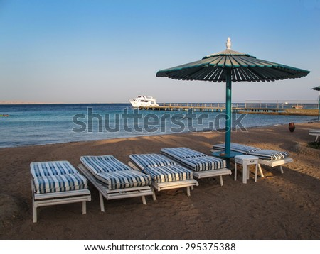 Beach with Four Chairs and Umbrella Calm late afternoon on the beach in Egypt. Four empty beach chairs and an umbrella. Sandy seashore. Water of the Red Sea. Yacht in the background. Blue evening sky. - stock photo