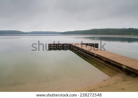 beach with jetty at lake - stock photo