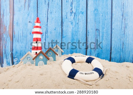 Beach with lighthouse and life buoy in front of vintage blue background - stock photo