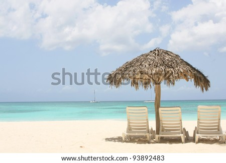 beach with palm tree and two chairs on sand - stock photo