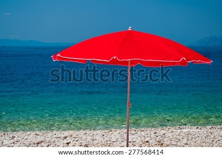 Beach with pebbles and red sunshade with sea in background on a summer day - stock photo