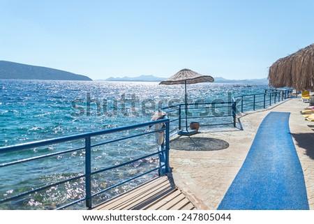 Beach with pier on Turkish resort, Bodrum, Turkey - stock photo