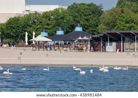 Beach with playground and swans on the Baltic Sea in city of Gdynia, Poland - stock photo