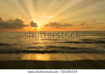 beach with rays during sunset - stock photo