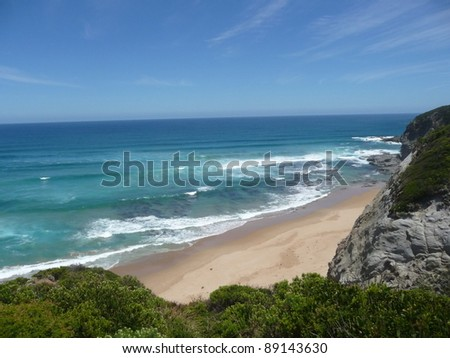 Beach with rock face and blue sea.