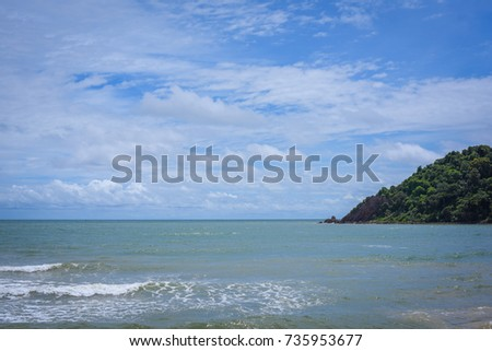 Beach with rocks and a cloudy sky for the background.