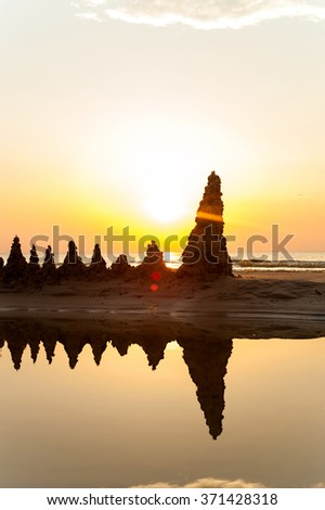 Beach with sandcastles on spectacular Baltic sea sunset background in Latvia. Multicolored summertime outdoors vertical image. - stock photo
