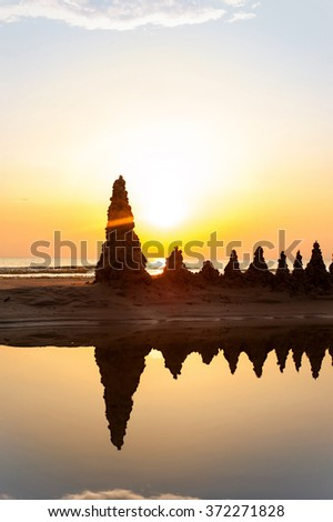 Beach with sandcastles on spectacular Baltic sea sunset background in Latvia. Multicolored summertime outdoors vertical image with filter. - stock photo