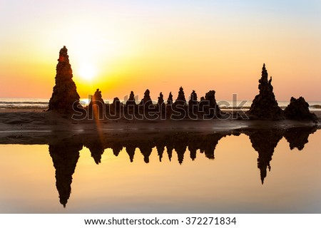 Beach with sandcastles on spectacular Baltic sea sunset background in Latvia. Multicolored summertime outdoors horizontal image with filter. - stock photo