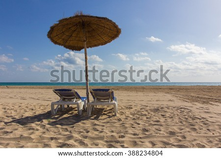Beach with umbrella and deckchairs, blue sky. Sunny day on vacation - stock photo