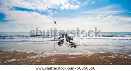 Beach with waterbreak and flag at Lido island, Venice, Italy - stock photo