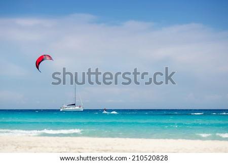 Beach with yacht and kitesurfer in Sardinia - stock photo