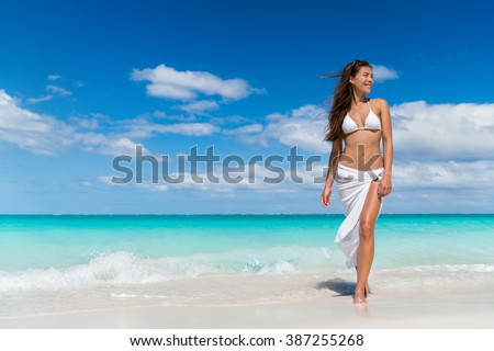 Beach woman in fashion beachwear white cover-up skirt clothing. Asian girl tourist wearing white pareo for sun protection relaxing walking in ocean water on summer vacation travel. - stock photo