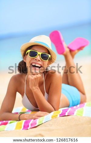 Beach woman laughing having fun in summer vacation holidays. Multiracial fashion hipster wearing sunglasses lying in the sand on colorful beach towel.
