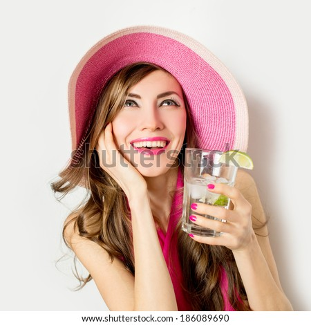 Beach woman laughing having fun in summer vacation holidays. Young woman wearing big straw hat and drinking summer cocktail over white. focus on face - stock photo