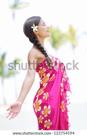 Beach woman on Hawaii relaxing enjoying the sun in serene relaxed pose. Hawaiian scene with beautiful mixed race Asian and Caucasian female model wearing sarong. - stock photo