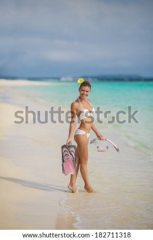 Beach woman snorkeling walking happy enjoying sun and holidays travel in sunny sunshine wearing bikini holding snorkel, fins and mask. Beautiful excited mixed race Asian Caucasian bikini girl. - stock photo