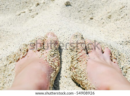 Beach - women's foot and the grains of sand - stock photo