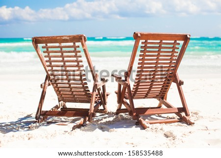 Beach wooden chairs for vacations and relax on tropical white sand plage - stock photo