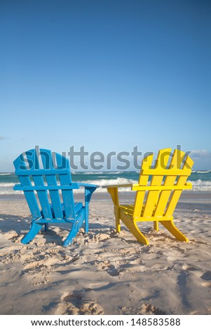 Beach wooden chairs for vacations and summer getaways in Tulum, Mexico - stock photo
