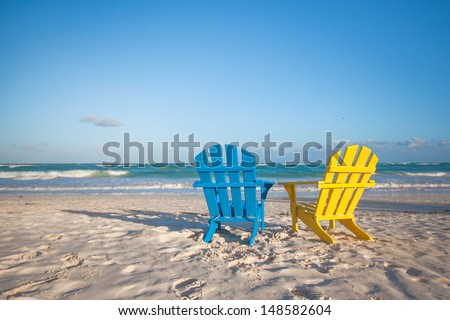 Beach wooden colorful chairs for vacations on tropical beach in Tulum, Mexico - stock photo