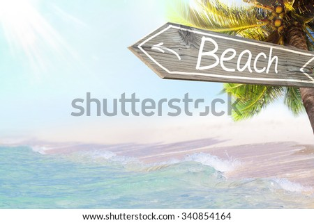 Beach wooden sign and blurry exotic beach background. Tropical landscape with coconut palm tree and white sand beach. Paradise design banner background. - stock photo