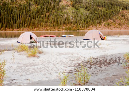 Beached canoes and two tents pitched on a sand bar alongside Yukon River, Yukon Territory, Canada, in remote boreal forest wilderness - stock photo