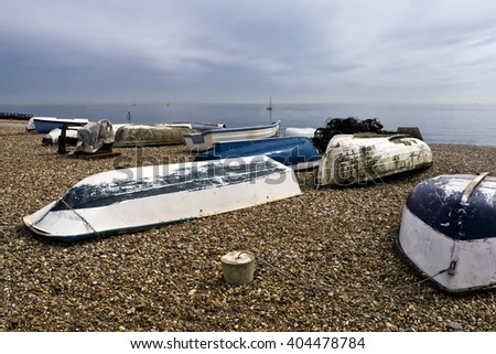Beached rowing boats; working boats beached on shingle  - stock photo
