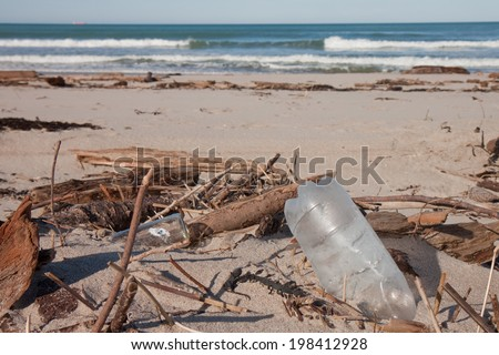 beached rubbish among storm debris on sand  - stock photo