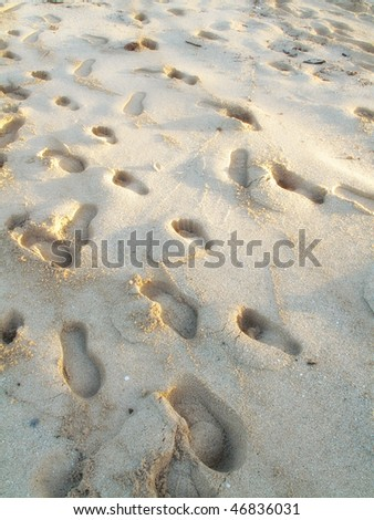 Beachwalk - footsteps in the sand an early morning - stock photo