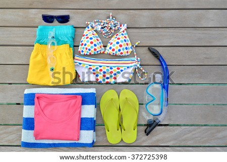 Beachwear from top view with sunglasses, goggles, bikini, sandal, short and towel. - stock photo