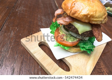 Beacon cheese burger with vegetables on wooden plate, useful for fast food concepts