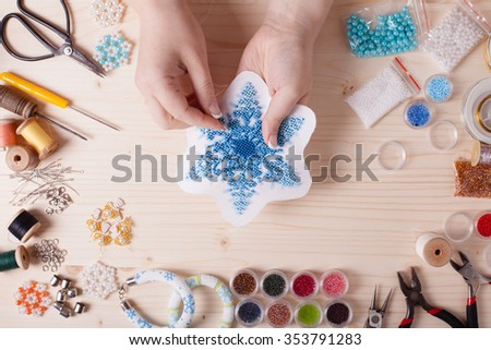 Beaded snowflakes for Christmas tree. Preparation for handmade, top view on the table