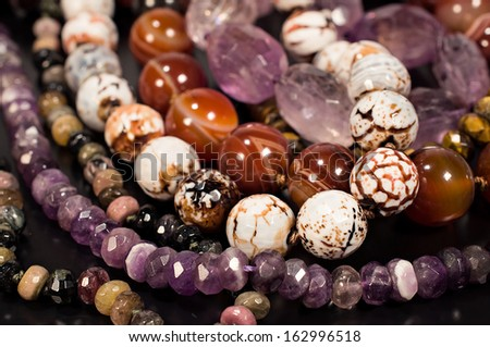 beads of different stones on a black background - stock photo